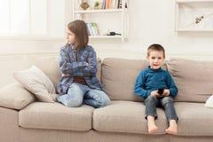 Deux enfants avec à télécommande sur le divan à la maison Photos stock