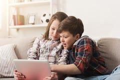 Deux enfants avec des instruments sur le divan à la maison Images libres de droits