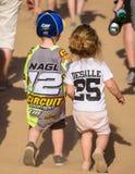 Deux enfants avec des motocross éventent des chemises marchant à l'événement de motocross photographie stock libre de droits