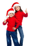 Deux enfants avec des pouces lèvent le signe et la Santa Photographie stock