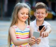 Deux enfants avec des téléphones portables dehors Photos libres de droits