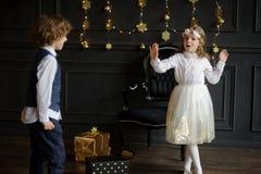 Deux enfants avec du charme se réjouissent aux cadeaux de Noël Photographie stock libre de droits