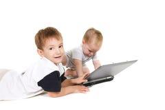 Deux enfants avec l'ordinateur portatif photos stock
