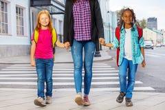 Deux enfants avec la femme marchant sur la rue Image libre de droits