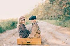 Deux enfants avec la grande valise jaune sur la route dans le rétro style Image stock