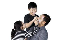 Deux enfants ayant l'amusement avec leur père Photos libres de droits