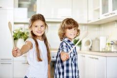 Deux enfants ayant l'amusement dans la cuisine avec des cuillères Image libre de droits