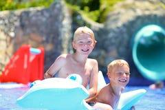 Deux enfants ayant l'amusement dans la piscine d'été Photographie stock libre de droits