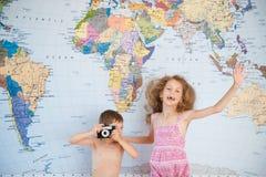 Deux enfants ayant l'amusement sur le fond de la carte du monde Photos stock