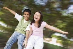 Deux enfants ayant l'amusement sur le rond point Photographie stock libre de droits