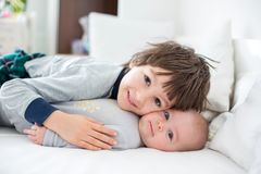 Deux enfants, bébé et son frère plus âgé dans le lit pendant le matin, Images stock