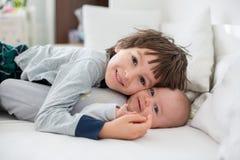 Deux enfants, bébé et son frère plus âgé dans le lit pendant le matin, Image libre de droits