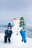 Deux enfants, bonhomme de neige de construction sur la montagne Images libres de droits