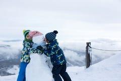 Deux enfants, bonhomme de neige de construction sur la montagne Photo stock
