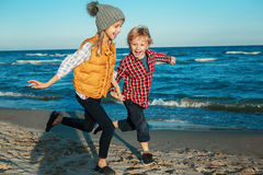 Deux enfants caucasiens blancs drôles badine des amis jouant le fonctionnement sur la plage de mer d'océan sur le coucher du sole Images stock