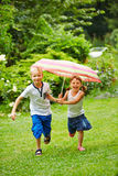 Deux enfants courant avec le parapluie sous la pluie photographie stock