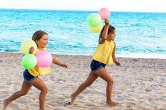 Deux enfants courant sur la plage avec des ballons de couleur Photographie stock libre de droits