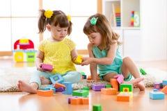 Deux enfants d'amis jouent ensemble dans le jardin d'enfants, la garde ou la maison Photographie stock libre de droits