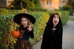 Deux enfants d'un plus jeune âge scolaire dans des costumes pour Halloween Photographie stock libre de droits
