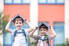 Deux enfants d'un plus jeune âge scolaire, du garçon et de son ami sont des livres de lecture sur l'herbe verte Photographie stock libre de droits