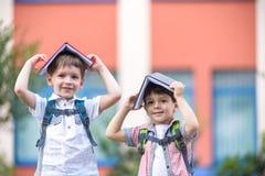 Deux enfants d'un plus jeune âge scolaire, du garçon et de son ami sont des livres de lecture sur l'herbe verte Photographie stock