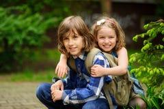 Deux enfants d'un plus jeune âge scolaire, le garçon et la fille, accroupi ayant embrassé Images libres de droits