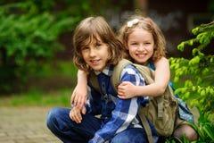 Deux enfants d'un plus jeune âge scolaire, le garçon et la fille, accroupi ayant embrassé Photo stock