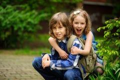 Deux enfants d'un plus jeune âge scolaire, le garçon et la fille, accroupi ayant embrassé Image libre de droits