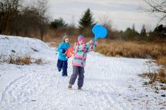 Deux enfants d'un plus jeune âge scolaire passent le temps dans le jour d'hiver avec plaisir Photos stock