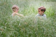 Deux enfants dans l'herbe Photographie stock