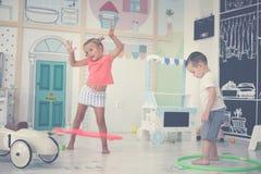 Deux enfants dans la cour de jeu Hoolahope de rotations d'enfants Photo libre de droits