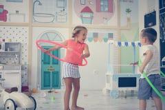 Deux enfants dans la cour de jeu Hoolahope de rotations d'enfants Image stock