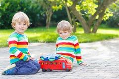 Deux enfants de mêmes parents, garçons d'enfant jouant avec l'autobus scolaire rouge Photo stock