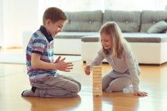 Deux enfants de mêmes parents heureux jouant un jeu avec les blocs en bois à la maison photographie stock
