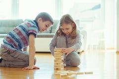 Deux enfants de mêmes parents heureux jouant un jeu avec les blocs en bois à la maison photo stock