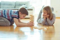 Deux enfants de mêmes parents heureux jouant un jeu avec les blocs en bois à la maison images stock