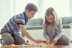 Deux enfants de mêmes parents heureux jouant un jeu avec les blocs en bois à la maison photos stock