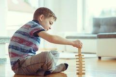 Deux enfants de mêmes parents heureux jouant un jeu avec les blocs en bois à la maison photographie stock libre de droits