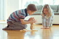 Deux enfants de mêmes parents heureux jouant un jeu avec les blocs en bois à la maison photos libres de droits