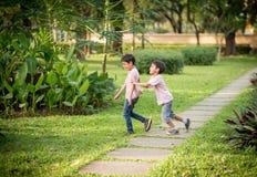 Deux enfants de mêmes parents jouant en parc Photo libre de droits
