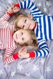 Deux enfants de mêmes parents mignons se trouvant sur le lit Frome de Fokus ci-dessus Photos stock