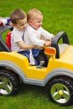 Deux enfants de mêmes parents dans la voiture de jouet Images stock