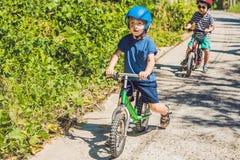 Deux enfants de petits garçons ayant l'amusement sur le vélo d'équilibre sur un pays Image libre de droits