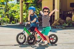 Deux enfants de petits garçons ayant l'amusement sur le vélo d'équilibre sur une route tropicale de pays Images libres de droits