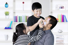 Deux enfants dessinant sur leur père Photo stock