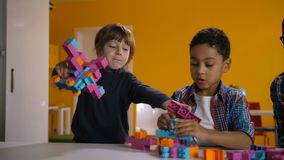 Deux enfants divers discutant au sujet du jouet dans le jardin d'enfants clips vidéos