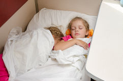 Deux enfants dorment sur le train sur le même emplacement au sol dans le chariot de seconde classe de compartiment Photo stock