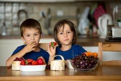 Deux enfants doux, frères de garçon, mangeant des fruits frais à la maison image libre de droits