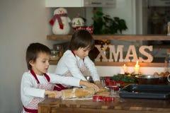 Deux enfants doux, frères de garçon, préparant des biscuits de pain d'épice Photos libres de droits