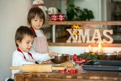Deux enfants doux, frères de garçon, préparant des biscuits de pain d'épice Image libre de droits